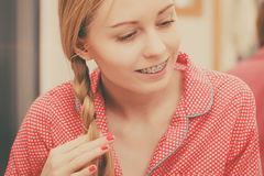 Woman doing braid on blonde hair. Fancy trendy blond hairstyle at home concept. Woman wearing pink pajamas doing braid on blonde hair Royalty Free Stock Image
