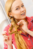 Woman doing braid on blonde hair. Fancy trendy blond hairstyle at home concept. Woman wearing pink pajamas doing braid on blonde hair Royalty Free Stock Photography