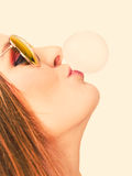 Woman doing bubble with chewing gum. Woman casual style teen girl doing bubble with chewing gum face profile closeup filtered photo. Youth style royalty free stock photography