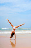 Woman doing cartwheel at the beach Royalty Free Stock Photography