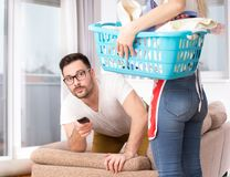 Woman doing chores while man watching tv Stock Photo