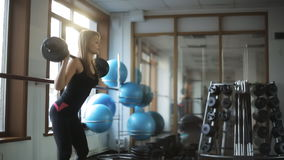 Woman doing classic squats with a barbell standing up, in a sports club. stock video