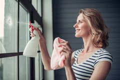 Woman doing cleaning at home. Beautiful young woman is doing cleaning at home. Holding cleaning tools and smiling Stock Images