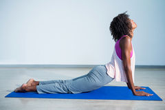 Woman doing cobra pose on exercise mat Royalty Free Stock Images