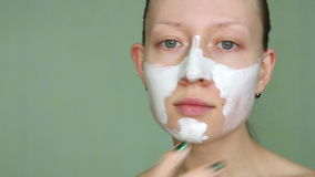 Woman doing cosmetic mask on her face.  stock video footage