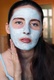 Woman doing cosmetic mask on her face Royalty Free Stock Image