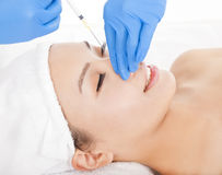 Woman is doing cosmetic surgery injections. Over white Stock Photo