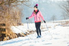Woman doing cross country skiing as winter sport. In snow landscape royalty free stock images
