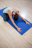 Woman doing cross legged forward fold on exercise mat royalty free stock photography