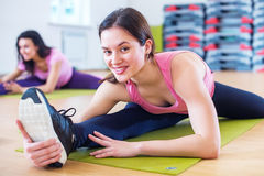 Woman doing cross split exercise working out her hip abductor muscles and ligaments. Fit female athlete stretching. Splits in gym Stock Image