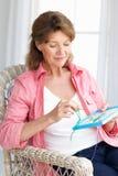 Woman doing cross stitch. Senior woman doing cross stitch royalty free stock photography