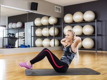 Woman Doing Crunches On Exercise Mat In Gym Stock Image