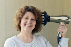 Woman doing curls with  hairdryer and diffuser Royalty Free Stock Images