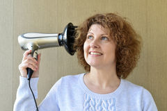 Woman doing curls with  hairdryer and diffuser Stock Images