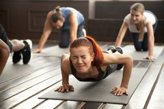 Woman doing difficult plank exercise or pushups at group trainin. Young fit sporty women with painful face expression doing hard difficult plank fitness exercise Stock Images