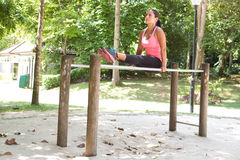 Woman doing dips exercise on balancing bar in park Royalty Free Stock Photos