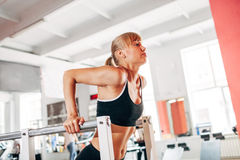 Woman doing dips in the gym. Athletic woman doing dips in the gym stock photo