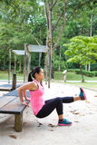 Woman doing dips on right leg in outdoor exercise park. Sporty woman doing dips on right leg in outdoor exercise park royalty free stock photography