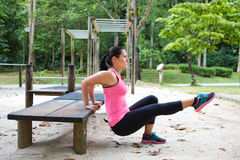 Woman doing dips on right leg in outdoor exercise park. Sporty woman doing dips on right leg in outdoor exercise park royalty free stock photos