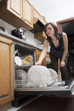 Woman doing dishes. Young woman in kitchen loading the dishwasher Stock Images
