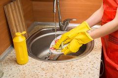 Woman doing the dishes at home kitchen. Woman doing the dishes at home kitchen Royalty Free Stock Image