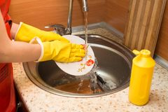 Woman doing the dishes at home kitchen. Woman doing the dishes at home kitchen Stock Photography