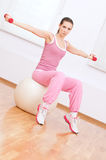 Woman doing dumbbell exercise at sport gym Stock Image