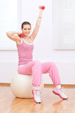 Woman doing dumbbell exercise at sport gym Stock Photos