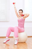 Woman doing dumbbell exercise at sport gym Stock Photo