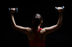 Woman doing shoulder press. A woman doing dumbbell shoulder press exercise with a dark background royalty free stock images