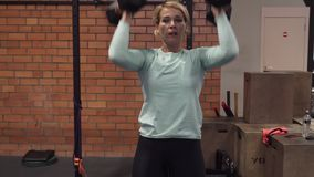 Woman doing dumbbell thruster exercise in gym stock footage