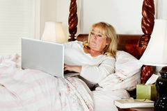 Woman doing e-mail in bed Stock Photo