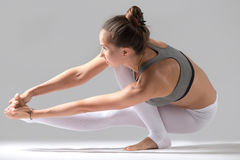 Woman doing Eka Pada Padangusthasana pose with squat Stock Images