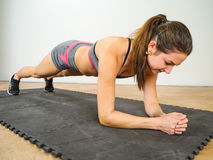 Woman doing elbow plank Stock Images