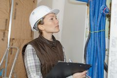 Woman doing electrical inspection royalty free stock photography