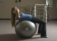 Woman doing exercise. Beautiful young blond woman doing abdominal crunches on an exercise ball in a fitness location Royalty Free Stock Photo