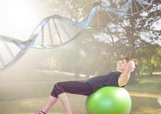 Woman doing exercise with the baal in the park. DNA chain over her Royalty Free Stock Images