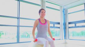 Woman doing exercise ball and dumbells. Video of woman doing exercise ball and dumbells stock video