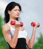 Woman doing exercise with dumbbell Stock Photo