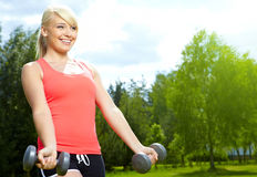 woman doing exercise with dumbbell in green park Stock Photo