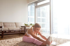 Woman doing exercise for flexibility increase. Pretty young woman stretching leg muscles while sitting on floor in living room and watching fitness video Stock Image