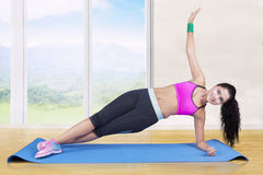Woman doing exercise with side plank pose Stock Image