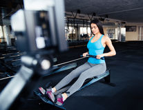 Woman doing exercise on simulator at gym Royalty Free Stock Image