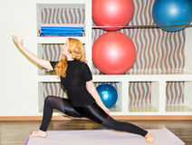 Woman doing exercise yoga and pilates pose on mat in gym. Asana. The concept of sport, fitness, training and health Royalty Free Stock Photography