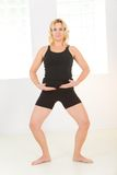 Woman doing exercises. Elder woman dressed sportswear working out. She's looking at camera. Front view royalty free stock images