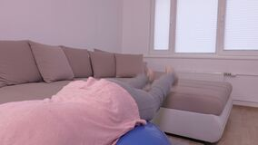 Woman doing exercises for back and abs. In room stock footage