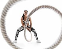 Woman doing exercises with battle rope. Photo of muscular model in military sportswear on white background. Strength and motivation royalty free stock photo