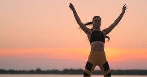 Woman doing exercises in the beach. A dark-haired woman coach in a sporty short top and gym leggings does sports stock video