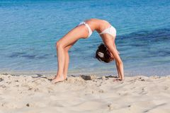 A woman is doing exercises on the beach Royalty Free Stock Photos