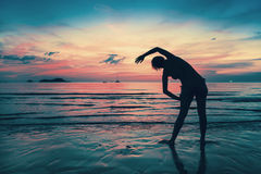 Woman doing exercises on the beach during sunset. Stock Images